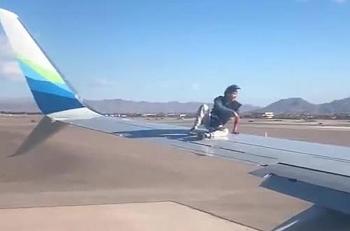 Hành khách vô tử cởi giày ngồi vắt vẻo trên cánh máy bay lúc chuẩn bị cất cánh