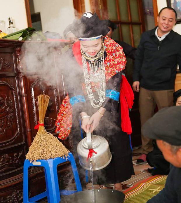 Cô dâu người Nùng thực hiện nghi thức đổ nước vào chảo khi về đến nhà trai trong ngày cưới.