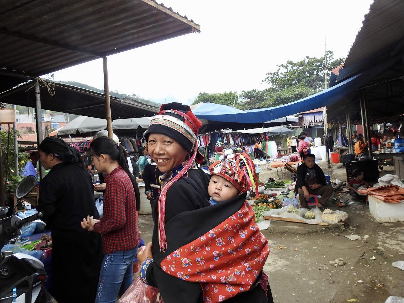Người mẹ dân tộc Dao địu con xuống chợ.