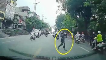 Cậu bé vòng tay, cúi đầu cảm ơn khi được tài xế nhường đường