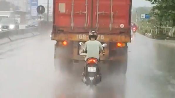 Camera giao thông: Tài xế xe máy liều lĩnh bám sát đuôi xe container để trú mưa