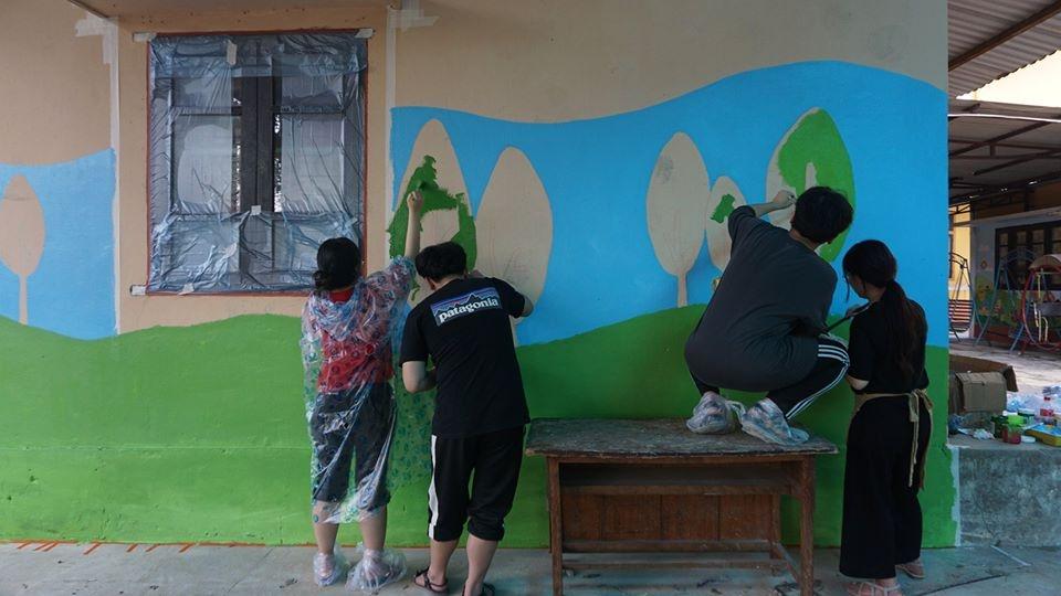 Các sinh viên Hàn Quốc trang trí bức tường của trường bằng những bức tranh đầy màu sắc.