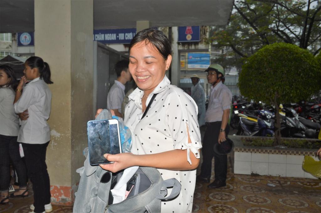 Một giáo viên giữ hàng chục điện thoại di động của các em học sinh trong buổi chiều bước vào thi môn Toán