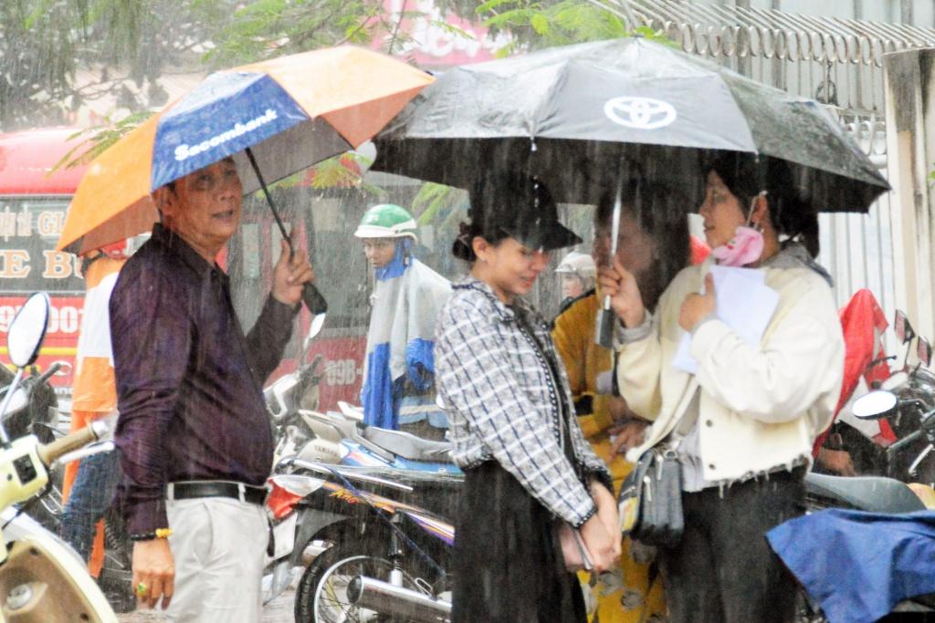 Các giáo viên đội mưa chờ các em thí sinh tham gia kỳ thi THPT Quốc gia